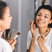 new beauty products june 2021   woman looking in the mirror as she does her makeup