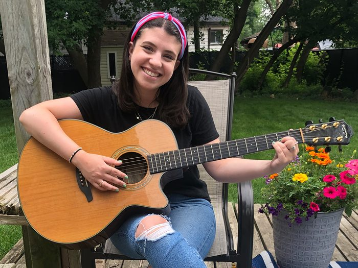 A young woman sits on a patio chair, smiling, with a guitar in her hands