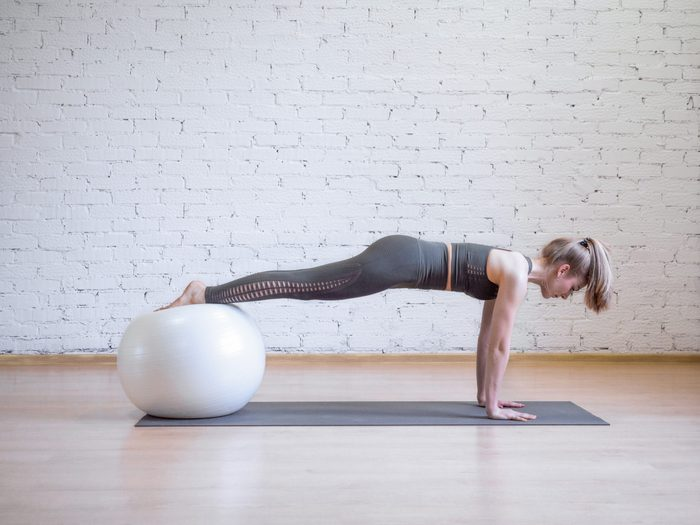 Caucasian,woman,doing,plank,position,using,math,and,fitness,ball,