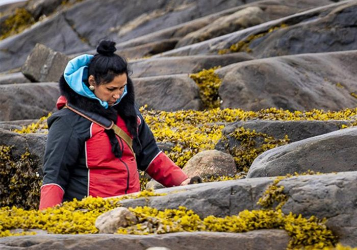 Bernice Clarke wears a red jacket and walks outside with a background of rocks and lichen