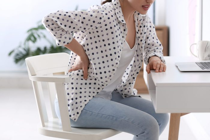 Woman,suffering,from,back,pain,in,office,,closeup.,bad,posture